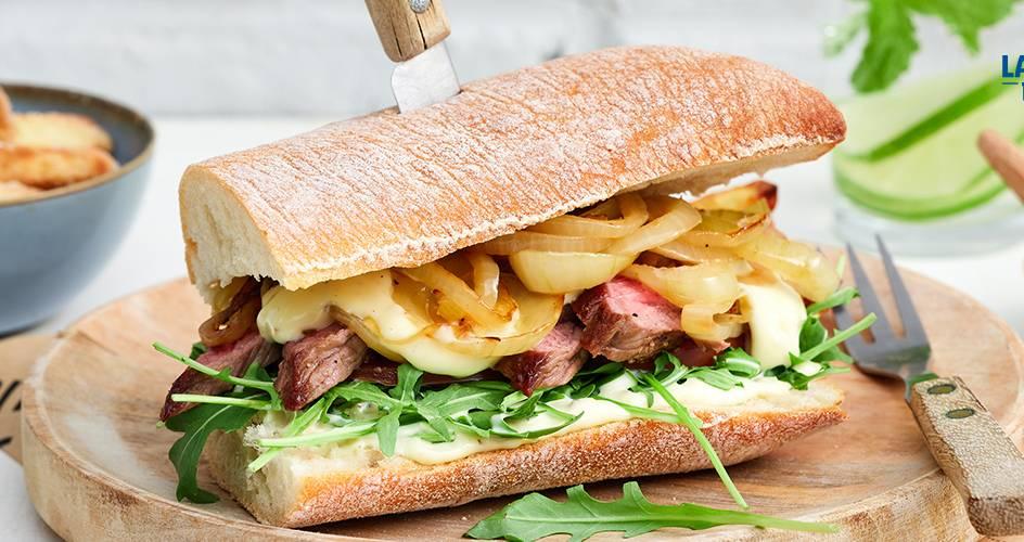 Sandwich américain : steak aux oignons caramélisés, sauce à l'ail et frites au four