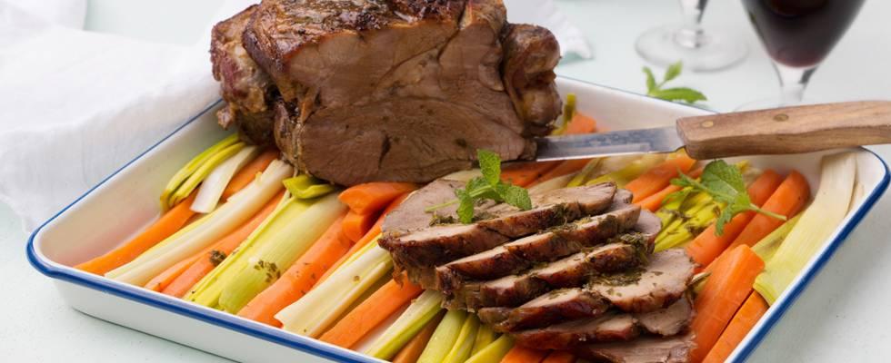 Gigot d'agneau sur un lit de poireau et carottes